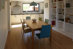 A photo of the dining room - a wooden table with six coloured chairs and some shelves