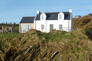 A photo of Barnacle Cottage taken from the beach