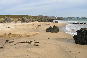 A photo of The Singing Sands beach with Carraig Fhada Lighthouse in the distance